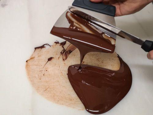 Atemperando el chocolate derretido en una mesa con espatulas
