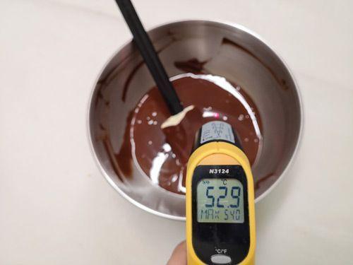 Comprobando la temperatura del chocolate con un termómetro para atemperar